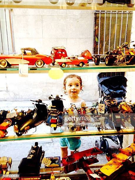 Cute Girl Looking At Toys From Glass Store Window