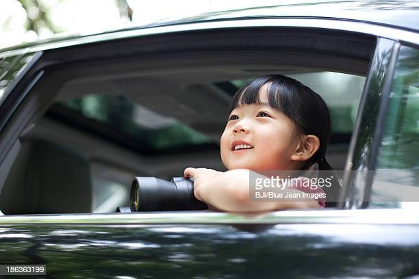 Cute girl looking through the car window with binoculars in hands