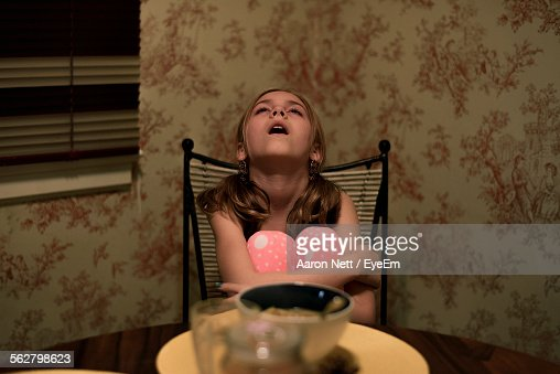 Cute Girl Looking Up While Sitting On Chair At Home