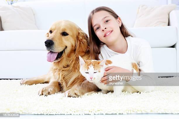 Carina ragazza sdraiata sul tappeto bianco con gli animali domestici.