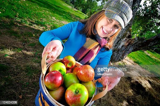 Cute Girl Offers Basket of Apples