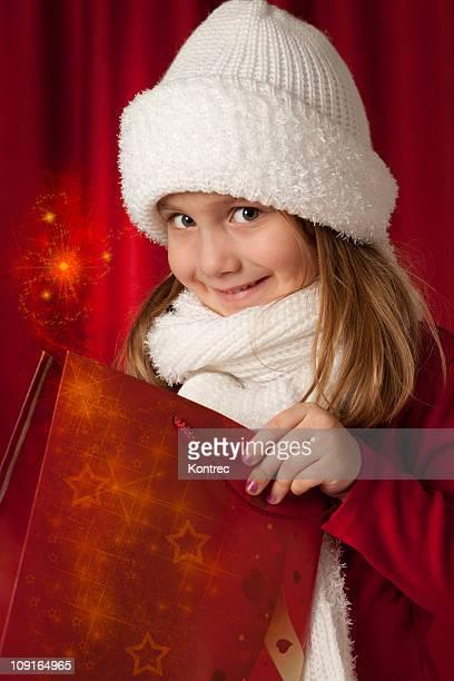 Cute girl opening her gift (Christmas magic)