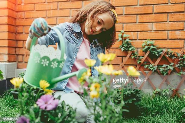 Rapariga engraçada Plantação de flores no seu arredores.