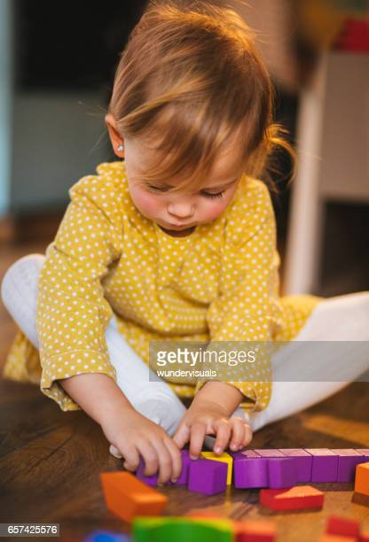 Cute girl playing with toy blocks in her room