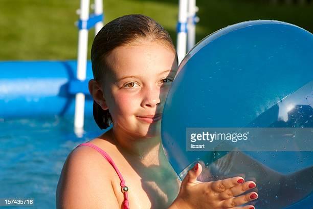 Jolie fille pose dans la piscine avec son ballon de plage