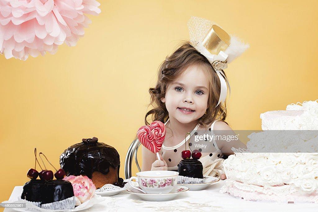Linda chica posando con dulces, sobre fondo amarillo : Foto de stock