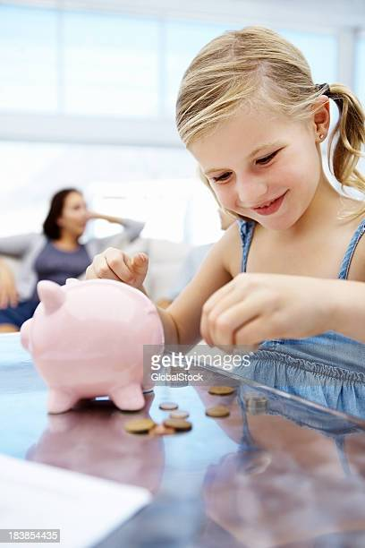 Cute girl putting money in piggy bank