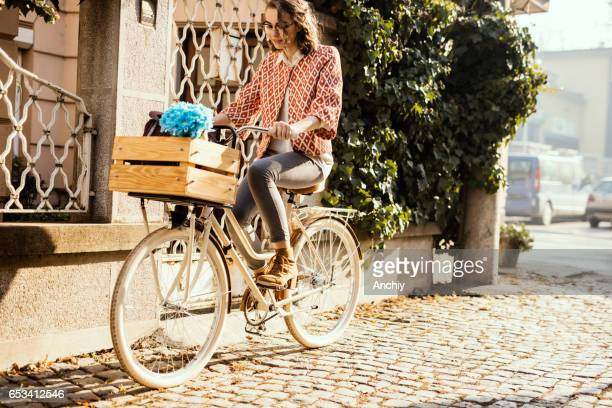 Cute girl riding a vintage bike on a paving stone