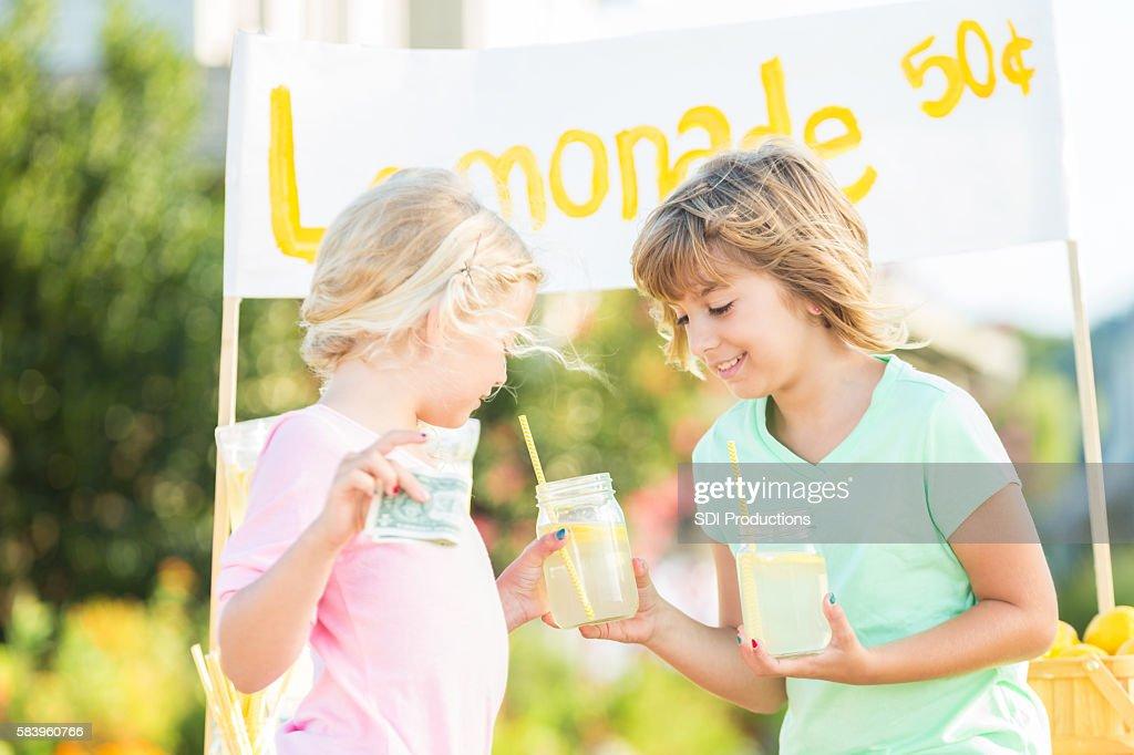 Cute girl selling glass of lemonade at her lemonade stand