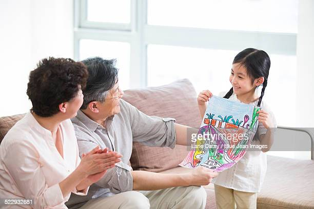 Cute girl showing drawing to grandparents
