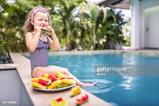 Joli fille assise près de la piscine et de salle à manger la pastèque