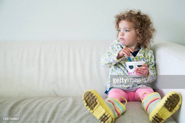 Cute Girl Sitting On Sofa At Home