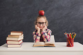 Portrait of cute smart girl in glasses with apple on head sitting with stack of books at table, copy space. Education and development concept