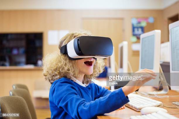 Cute girl using virtual reality goggle at school