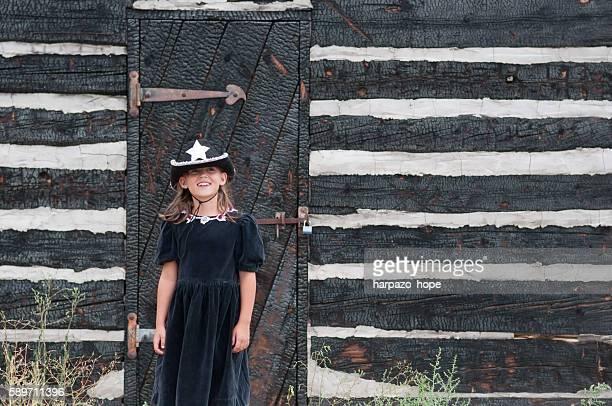 Cute girl wearing a black cowboy hat.