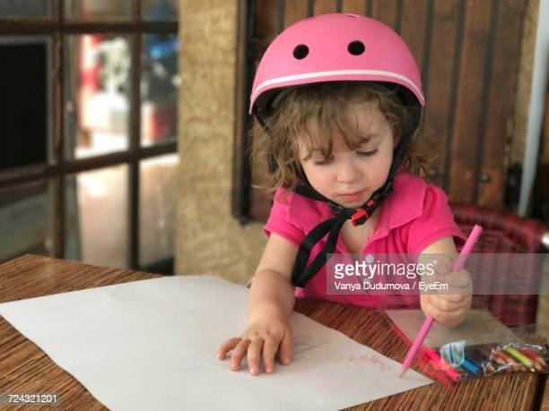 Cute Girl Wearing Pink Helmet While Drawing On Paper At Table
