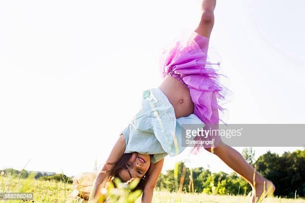 Cute girl wearing tutu cartwheeling in park