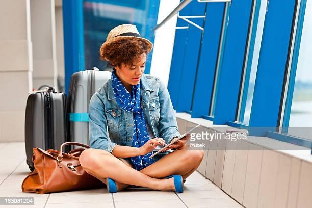 Ragazza carina con una tavoletta digitale presso l'aeroporto