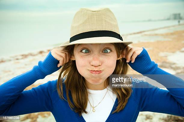 Cute girl with hat making a funny face on beach.