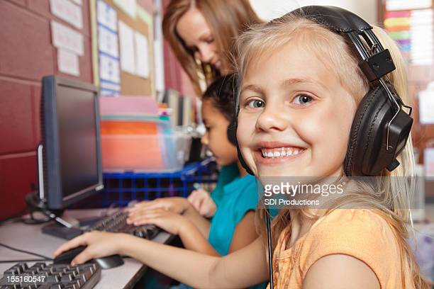 Cute Girl With Headphones Working on Computer at School