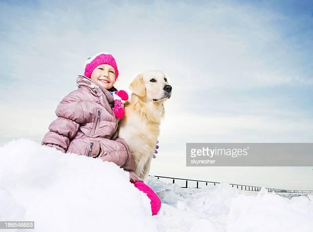 Süßes Mädchen mit Ihrem Hund mit Schnee genießen.