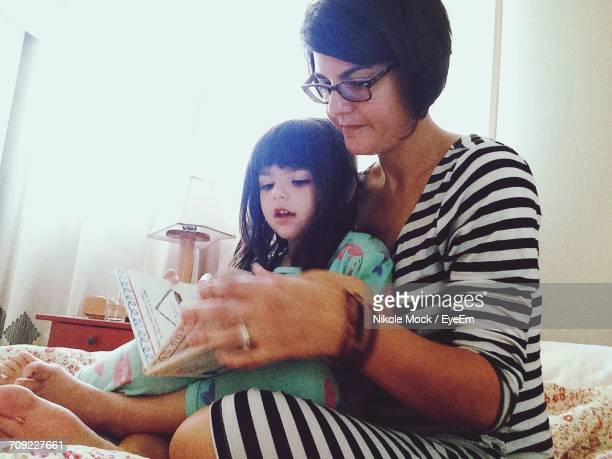 Cute Girl With Mother Reading Book In Bedroom