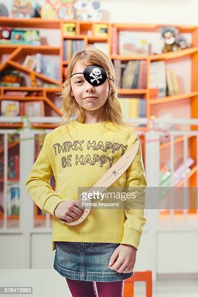 cute girl with pirate eye patch and wooden sword