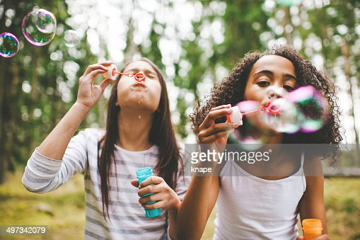 Cute girls blowing bubbles outdoors : Stock Photo