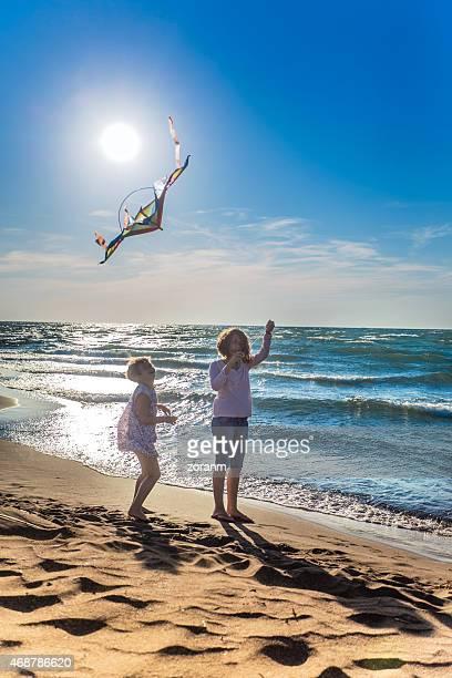 Bonitos Meninas voar um kite em uma Praia