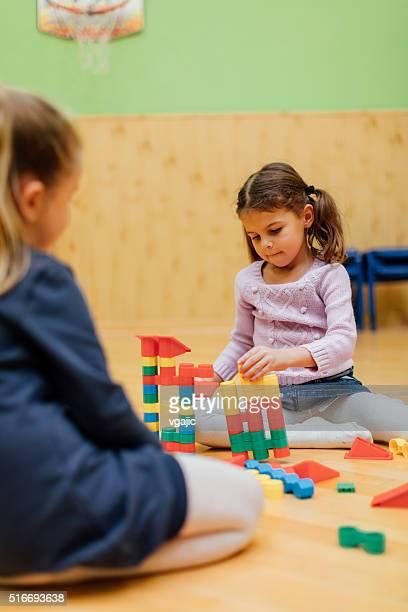 Niedlich Mädchen spielen mit Blöcke auf bereits im Kindergarten