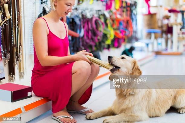Fofo golden retriever com grande osso em Loja de Animais de Estimação
