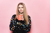 Cute happy girl hold coffee mug and looking up to the side and dreaming. Woman drinking coffee near pink wall.