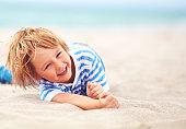 cute happy laughing boy, kid having fun on sandy beach, summer vacation