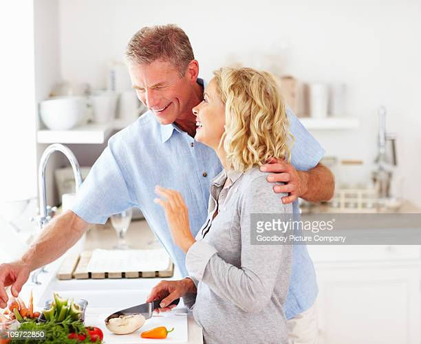 Cute happy mature couple preparing food in kitchen