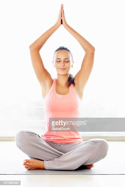 Cute happy woman meditating with hands joined over head