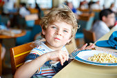 Cute healthy preschool kid boy eats pasta noodles sitting in school or nursery cafe. Happy child eating healthy organic and vegan food in restaurant. Childhood, health concept