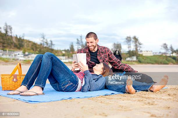 Cute heterosexual couple sitting on a blanket and reading