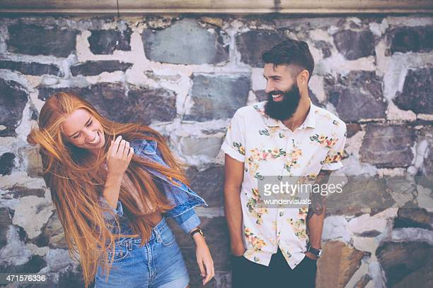 Cute hipster couple laughing in front of a stone wall