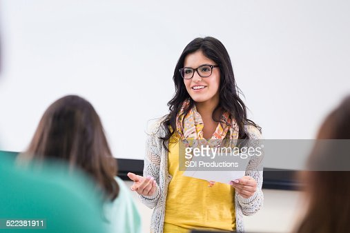 Cute hipster student reading report in front of classmates