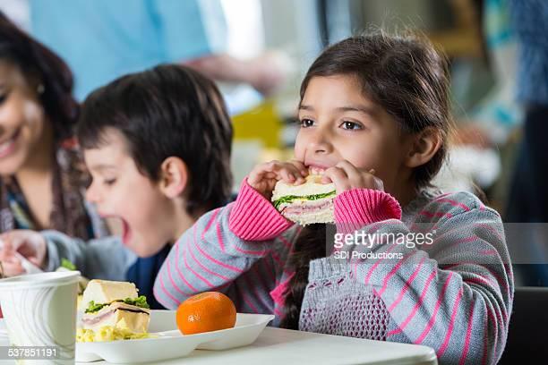 Carina ragazza ispanica mangiare pasto in cucina della community food bank