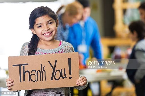 Cute Hispanic girl holding THANK YOU sign at food bank