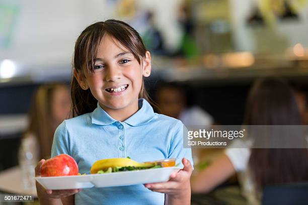 Cute Hispanic girl in private school cafeteria lunchroom