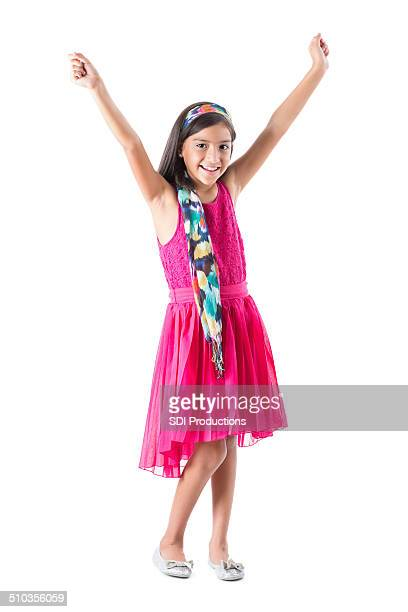 Cute Hispanic little girl raising arms excitedly