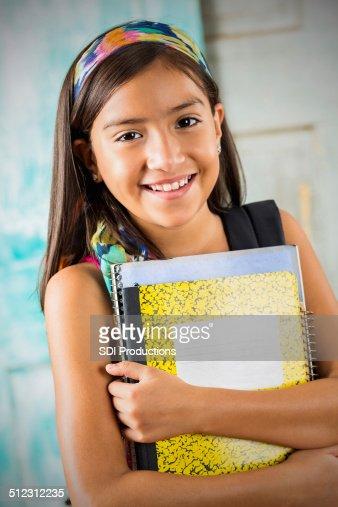 Cute Hispanic student holding books before school starts