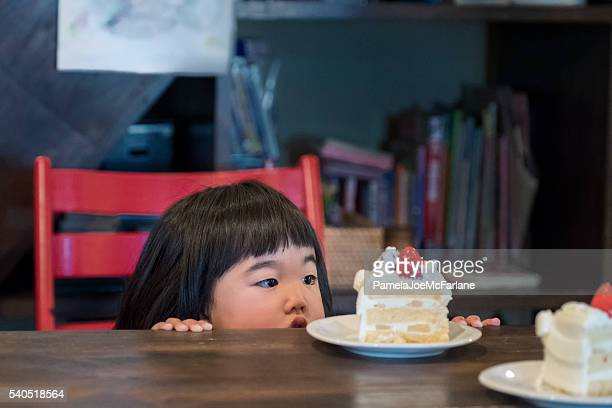 Cute Japanese Toddler Girl Looking at Birthday Cake on Table