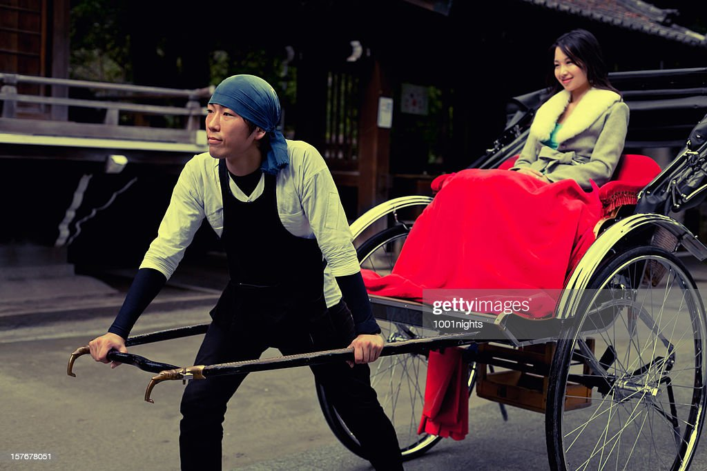 Cute Japanese woman pulled by a rickshaw : Stock Photo