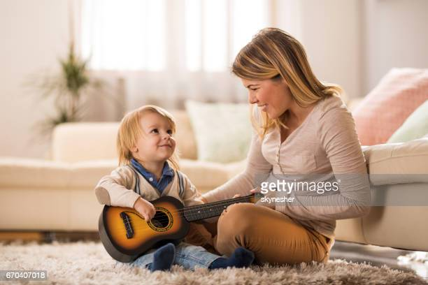 Cute kid learning to play acoustic guitar with a help of his mother at home.