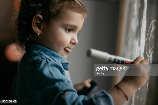 Cute kid with tongue out drawing on the window