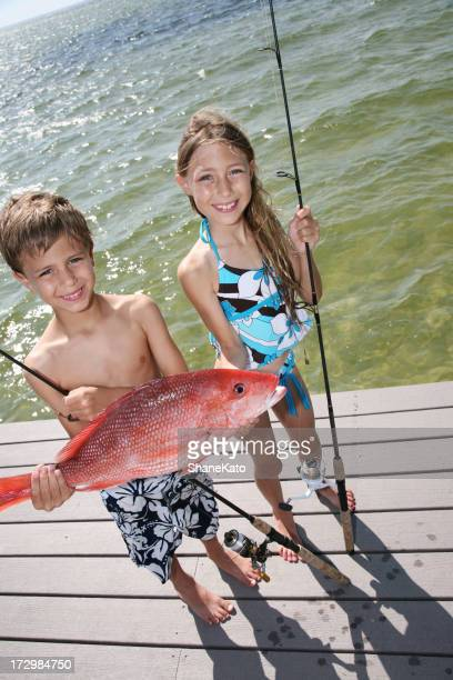 Cute kids fishing show off their red snapper catch