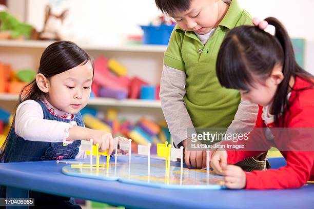 Cute kindergarten children placing flags on world map